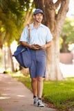 Почтальон идя вдоль улицы поставляя письма Стоковые Изображения