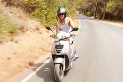 年轻人骑马沿乡下公路的小型摩托车 免版税库存图片