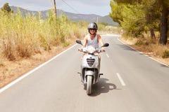 年轻人骑马沿乡下公路的小型摩托车 库存照片