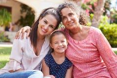 祖母在有女儿和孙女的庭院里 免版税库存照片