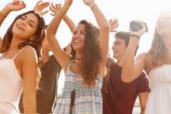 跳舞户外反对太阳的小组少年朋友 免版税图库摄影