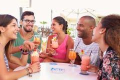 喝鸡尾酒的小组朋友在室外酒吧 免版税库存照片