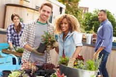 一起种植屋顶庭院的小组朋友 免版税库存图片