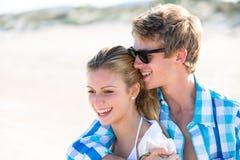白肤金发的青少年的夫妇在室外的海滩一起拥抱 免版税库存图片