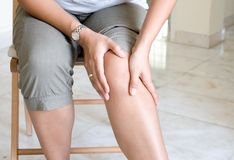 膝盖痛苦遭受的妇女 库存照片