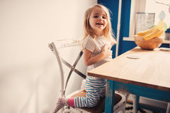 获得逗人喜爱的愉快的女婴在厨房的乐趣 库存照片