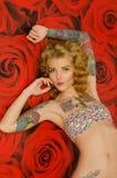 Татуированная женщина в предпосылке с цветками Стоковое фото RF