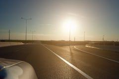 Οδήγηση στην εθνική οδό στο ηλιοβασίλεμα Στοκ Φωτογραφίες
