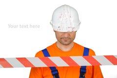 事故场面安全帽有血液的和警告磁带的受伤的民工在白色 库存图片