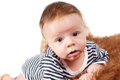 说谎在毛皮的可爱的男婴画象  库存照片