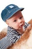 可爱的孩子画象说谎在毛皮的帽子的 免版税库存图片