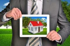 Κτηματομεσίτης που παρουσιάζει φωτογραφία με το σπίτι στην ταμπλέτα Στοκ φωτογραφία με δικαίωμα ελεύθερης χρήσης