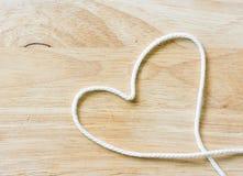 Веревочка сердца на деревянном Стоковое Изображение