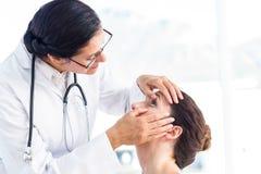 检查她的患者眼睛的医生 免版税库存图片