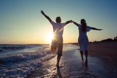 Ευτυχές ζεύγος που τρέχει στην παραλία Στοκ Εικόνα