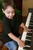 рояль мальчика играя детенышей Стоковое Изображение