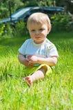 小男孩在夏天公园坐草 免版税库存图片