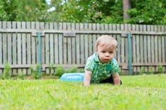 爬行在草的逗人喜爱的婴孩 库存图片