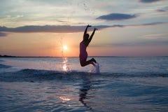 Κορίτσι που έχει τη διασκέδαση στην παραλία θάλασσας Στοκ Εικόνες