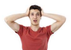 Изумленная рука молодого человека держа голову Стоковые Фото