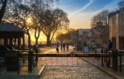 太阳集合的塔公园 与休息由水的人的泰晤士河人行道 伦敦 库存照片