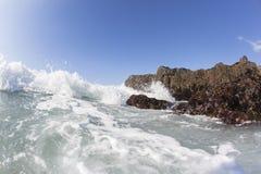 波浪浪端的白色泡沫碰撞的岩石海滩 免版税图库摄影