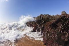 波浪浪端的白色泡沫碰撞的岩石海滩 免版税库存图片