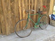 老牌生锈的绿色自行车和木墙壁 免版税库存图片