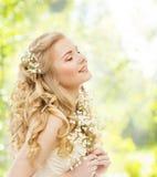 愉快的作的妇女,有花的,闭合的眼睛女孩 免版税库存照片