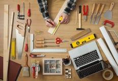 测量一个木板条的人 免版税库存图片