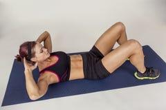 做咬嚼仰卧起坐的坚强的美丽的健身妇女 免版税库存照片
