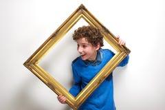 拿着画框的快乐的小男孩 免版税库存图片