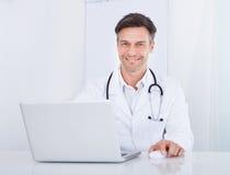 医生膝上型计算机使用 免版税库存照片