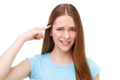 打手势手指的年轻美丽的妇女反对她的寺庙 查出在白色 免版税库存图片
