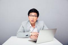 坐在与膝上型计算机的桌上的惊奇的商人 免版税库存图片