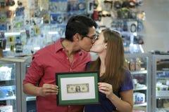 Ευτυχείς ιδιοκτήτες μαγαζιό που φιλούν και που παρουσιάζουν πρώτο δολάριο Στοκ εικόνες με δικαίωμα ελεύθερης χρήσης
