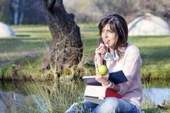 少妇学习的和听的音乐在秋天公园 免版税库存照片
