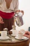 妇女拿着水壶和倒的茶入杯子 免版税库存照片