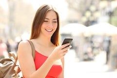 使用一个巧妙的电话的妇女在街道在夏天 免版税库存图片