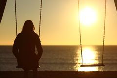 孤独的单独妇女观看的日落在冬天 免版税库存照片