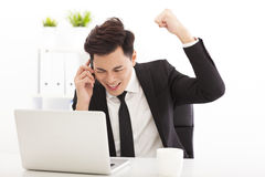 Счастливый бизнесмен говоря на телефоне в офисе Стоковые Изображения RF