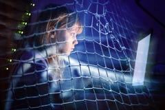 研究膝上型计算机的小女孩在一个捕鱼网的晚上 免版税库存照片