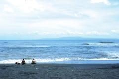 在海洋和海滩的一天与黑沙子 免版税库存照片
