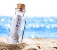 Бутылка с сообщением для помощи Стоковые Фото