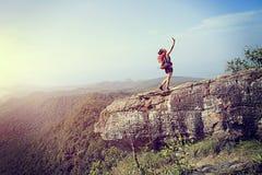 拍与巧妙的电话的妇女远足者照片在山峰 免版税图库摄影