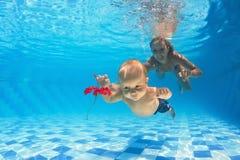 有妇女潜水的孩子在水池的一朵红色花的 库存照片
