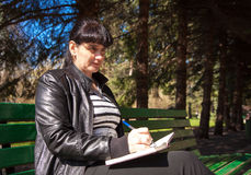 写笔的年轻美丽的妇女在笔记本 库存图片