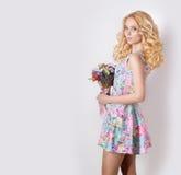 有站立在与淡紫色花花束的白色背景的卷曲金发的美丽的性感的谦虚甜嫩女孩  库存图片