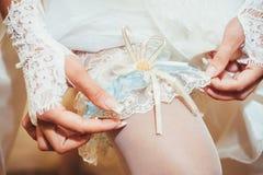 把婚礼袜带放的新娘在她的腿上 免版税库存照片