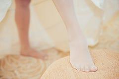 把婚礼袜带放的新娘在她的腿上 免版税库存图片